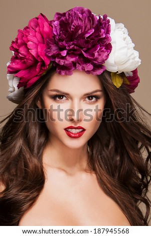 beautiful woman with bright flowers on her head - stock photo