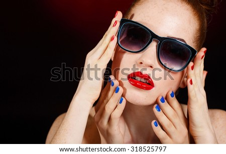 Beautiful woman with bright make-up and sunglasses. Beautiful red hair young woman with two pair of hands. Mae up. Manicured nails. Studio photo.
