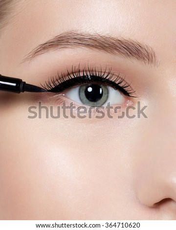 Beautiful woman with bright make up eye with sexy black liner makeup. Fashion arrow shape. Chic evening make-up. Makeup beauty with brush eye liner on pretty woman face - stock photo