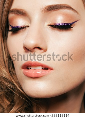 Beautiful woman with bright make up eye with sexy violet liner makeup. Fashion glitter arrow shape on woman's eyelid. Chic evening make-up - stock photo