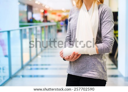 Beautiful woman with broken arm inside of a shopping center - stock photo