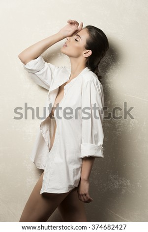 beautiful woman with brown hair and perfect skin in fashion pose with unbuttoned white shirt and nude legs
