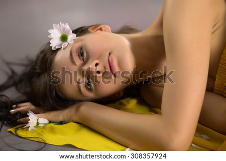 Beautiful woman with camomile in yellow dress