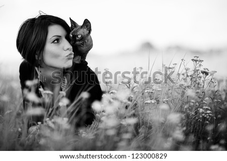 Beautiful woman with cat lying in a grass