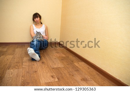 Beautiful woman with cat sitting on the floor