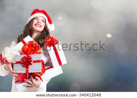 Beautiful woman with Christmas gifts on a light background. - stock photo