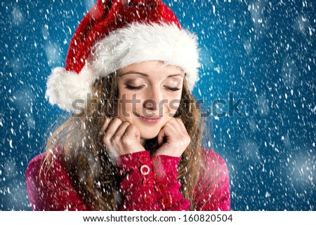 Beautiful woman with christmas hat on blue winter background with snowflakes