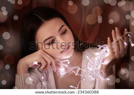 beautiful woman with Christmas light garland - stock photo