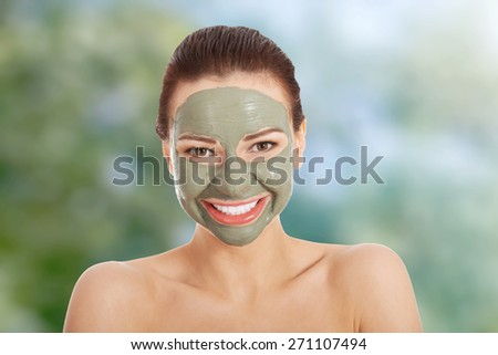 Beautiful woman with clay facial mask. - stock photo