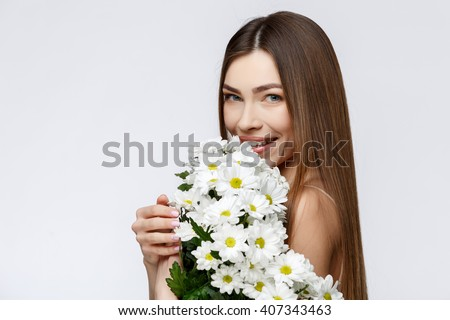 Beautiful Woman with Clean Fresh Skin holding flowers