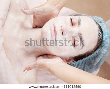 Beautiful woman with clear skin getting facial mask at salon - stock photo