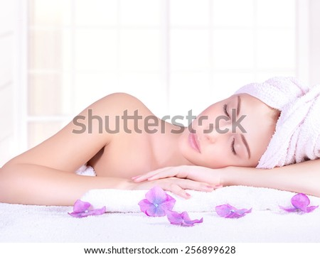 Beautiful woman with closed eyes lying down on massage table, enjoying day spa, luxury beauty salon, healthy lifestyle - stock photo