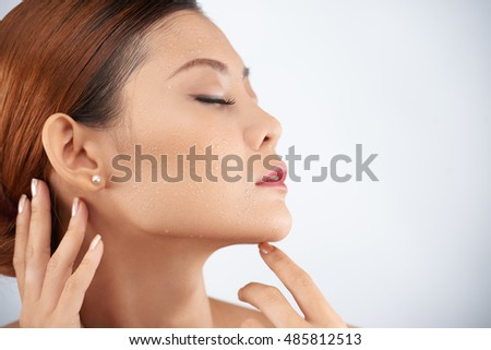 Beautiful woman with closed eyes touching her skin