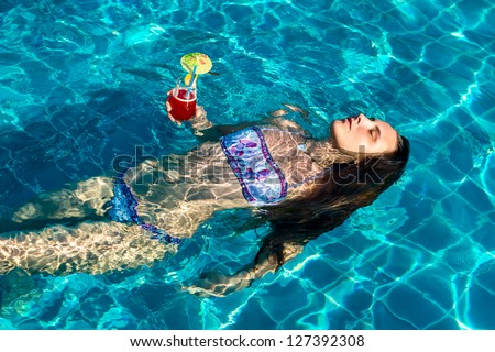 Beautiful woman with cocktail floating in pool on his back, in hot summer day - stock photo