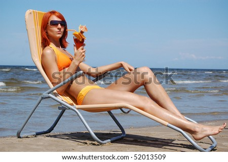 Beautiful woman with cocktail on the beach