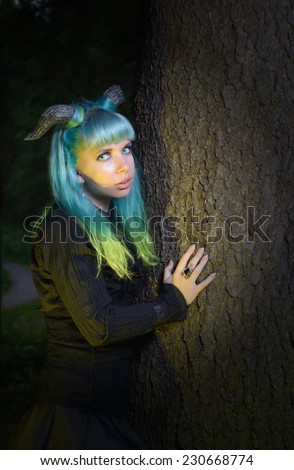 Beautiful woman with color hair and horns in the forest holds a tree