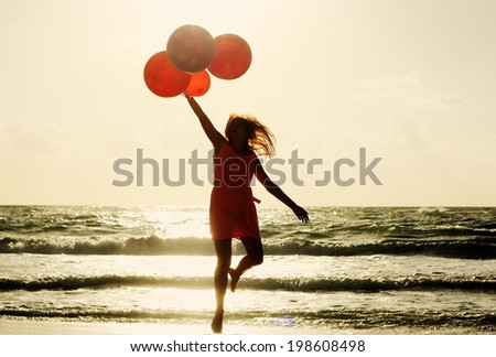 beautiful woman with colorful balloons on seaside - stock photo