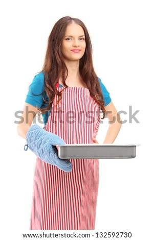 Beautiful woman with cooking mittens and apron holding a baking tray isolated on white background - stock photo