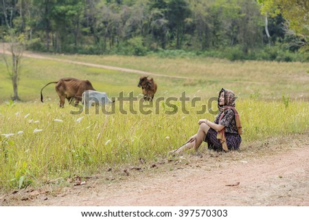 Beautiful woman with cow in green meadow