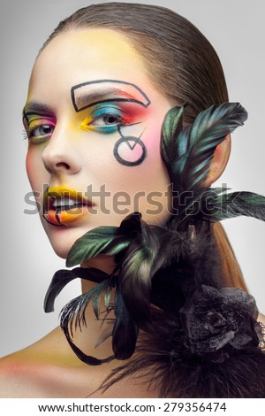 Beautiful woman with creative makeup and pearl feathers on gray background