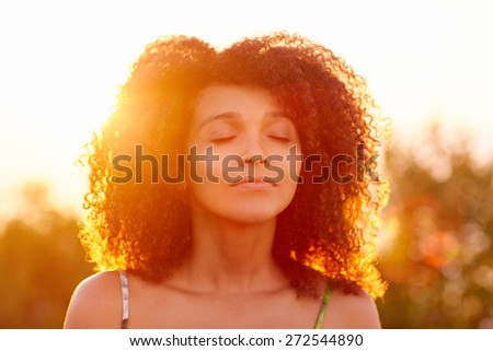 Beautiful woman with curly afro hair looking relaxed and happy with her eyes closed against a golden sunset with sun flare  - stock photo