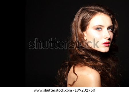 Beautiful woman with curly hair and evening make up. Fashion