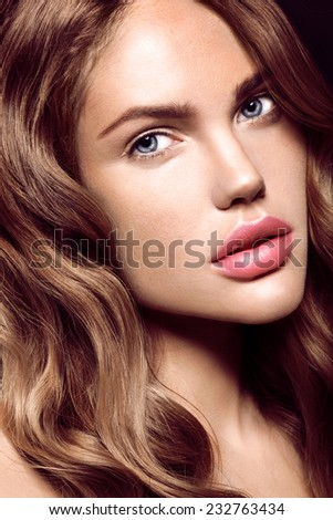 Beautiful woman with curly hair and evening make up. Fashion - stock photo