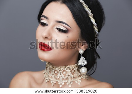 Beautiful woman with curly hair and evening make-up. Jewelry and Beauty. Fashion art photo - stock photo