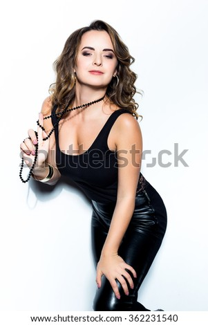 Beautiful Woman with Curly Hair dressed in a black T-shirt and leather pants in white background