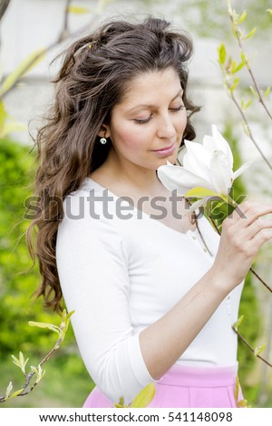 beautiful woman with curly hair smelling magnolia flower
