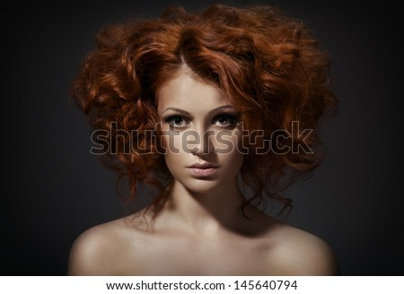 Beautiful woman with curly hairstyle against dark background - stock photo