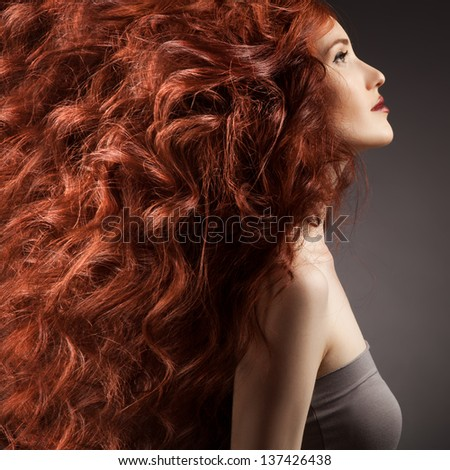 Beautiful woman with curly hairstyle against gray background - stock photo