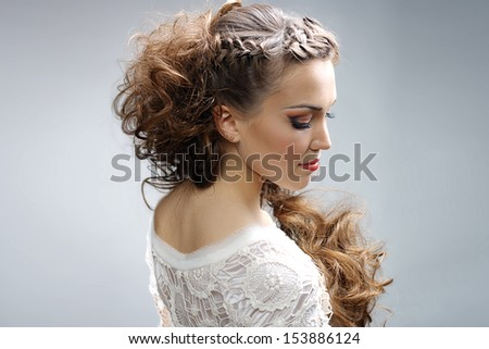 Beautiful woman with curly hairstyle against gray background