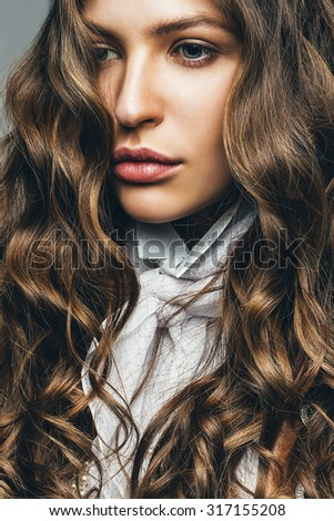 beautiful woman with curly long hair in studio