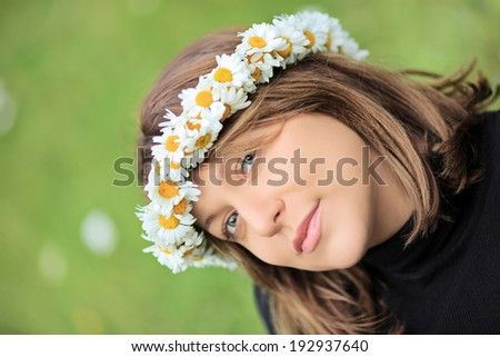Beautiful woman with daisy hair wreath posing outdoors