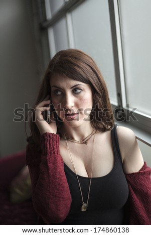 Beautiful woman with dark brown hair and blue eyes talking on her cell phone. - stock photo