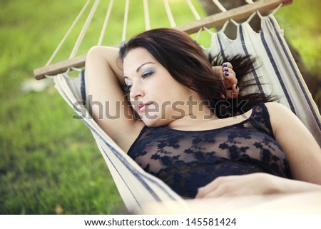 Beautiful woman with dark hair lying in a hammock in the summer and looking dreamily into the distance. - stock photo