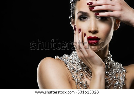 beautiful woman with dark makeup and red lipstick posing on black background. Wearing silver disco ball jewllery.