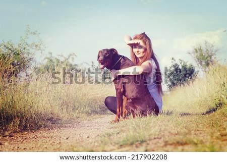 beautiful woman with doberman dog - stock photo