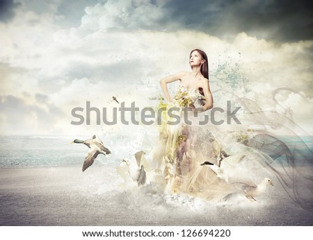 beautiful woman with dress with flowers and birds on the beach - stock photo