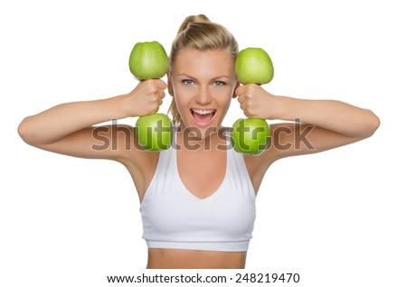 Beautiful woman with dumbbells from ripe apples isolated on white - stock photo