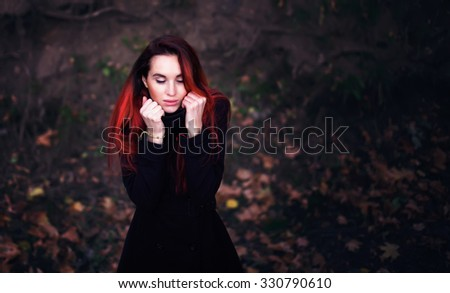 Beautiful woman with dyed red hair in a warm coat bundling up to keep herself warm during cold autumn weather. Hipster woman shivering. - stock photo