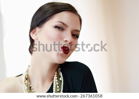 Beautiful woman with evening make-up. Jewelry and Beauty. Smile, giving a kiss - stock photo