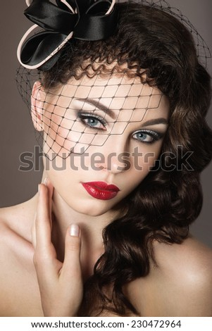 Beautiful woman with evening make-up, red lips and curls. Beauty face. Picture taken in the studio on a gray background.