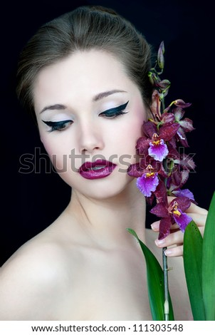 Beautiful woman with evening make-up with orchid