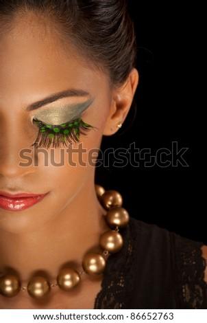 Beautiful woman with eyelashes made up of bird feathers - stock photo