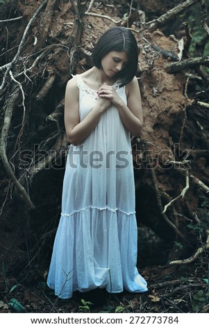 Beautiful woman with eyes closed praying among dead trees . Dark fantasy