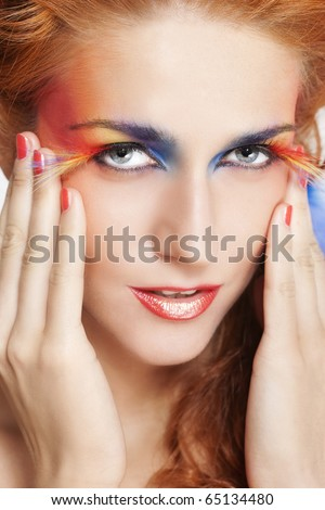 Beautiful woman with face framed in feathers with bright makeup and long faux lashes - stock photo