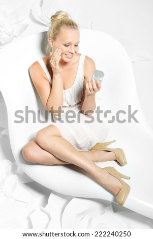 Beautiful woman with facial cream .Beautiful young woman sitting on a white chair surrounded by stylish white flowers  - stock photo