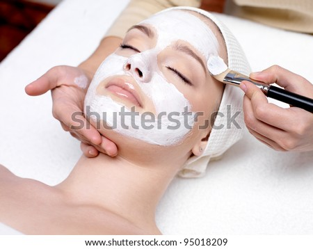 Beautiful woman with facial mask at beauty salon